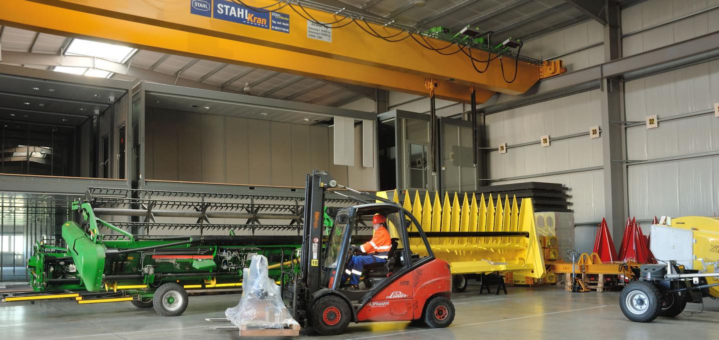 Oben sieht man einen stationären Kran für 38 Tonnen Last in gelb. Darunter stehen zwei Maschinen in grün und gelb, davor transportiert ein Gabelstapler eine Palette mit Ware.