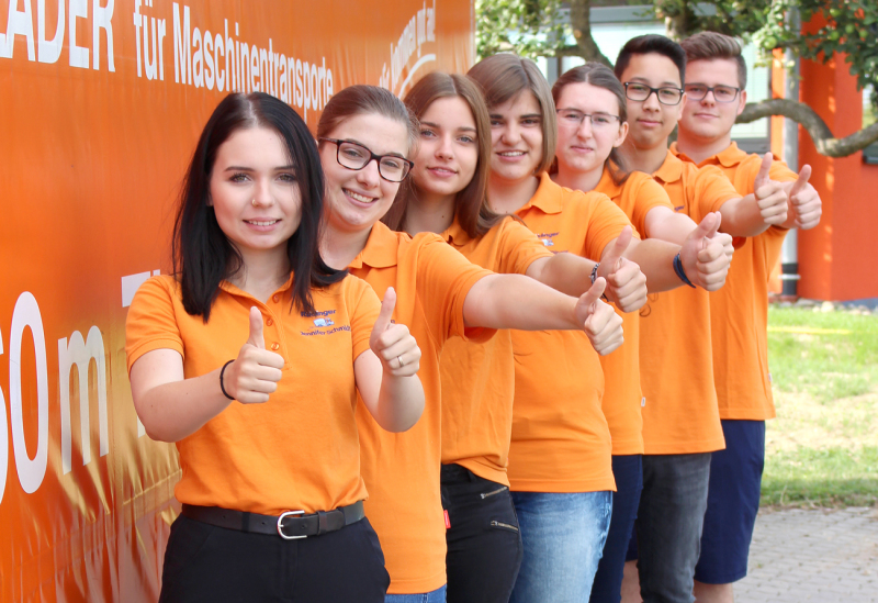 """Neben einem Lkw mit orangener Plane stehen 7 Jugenldiche seitlich versetzt hintereinander und heben die Daumen zum """"okay"""". Alle haben orangene T-Shirts an."""