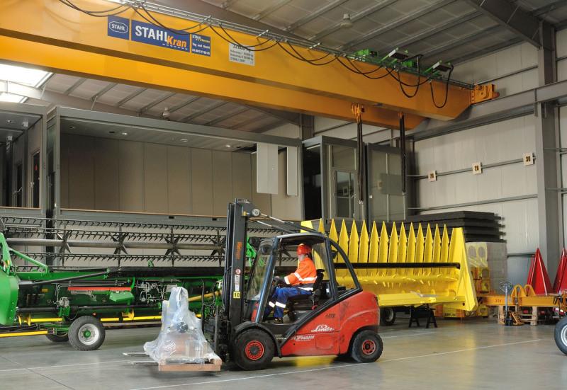 Im oberen Teil des Bildes eine Kranlager sieht man den 38-Tonnen-Kran, vorne beziehungsweise unten sieht man einen Gabelstapler mit einer verpackten Maschine. Dahinter sind 2 weitere Maschinen.
