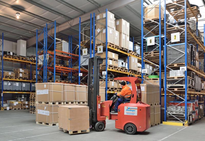 Ein roter Gabelstapler steht vor mehreren Reihen an Paletten-Regalen in einer Lagerhalle. Er hat eine Holzkiste auf seinen Gabeln. Ein Mitarbeiter in orange/blauer Kleidung fährt ihn.