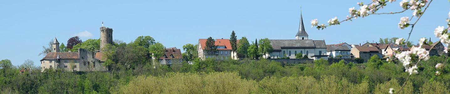 In einem Superbreitformat sieht man das obere Krautheim auf dem Berg: Links ist die Burg, in der rechten Hälfte zunächst die Kirche, daneben Häuser. Ein blühender Zweig hängt rechts ins Bild.