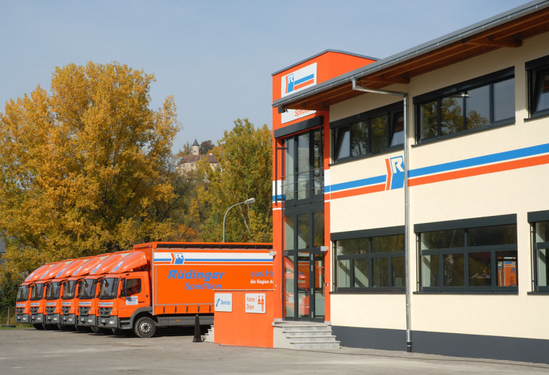 Die linke Hälfte des modernen, neuen Gebäudes der Spedition. Links daneben sind 6 kleine Lkw und dahinter sieht man Bäume im beginnenden Herbstlaub.