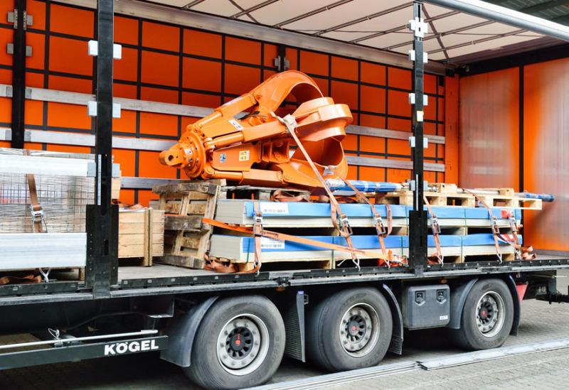 Ein seitlich offener Lkw, ein Planentieflader, ein 40-Tonnen-Lkw der Spedition ist seitlich offen und man sieht eine große graue Maschine geladen, die nicht verpackt ist.