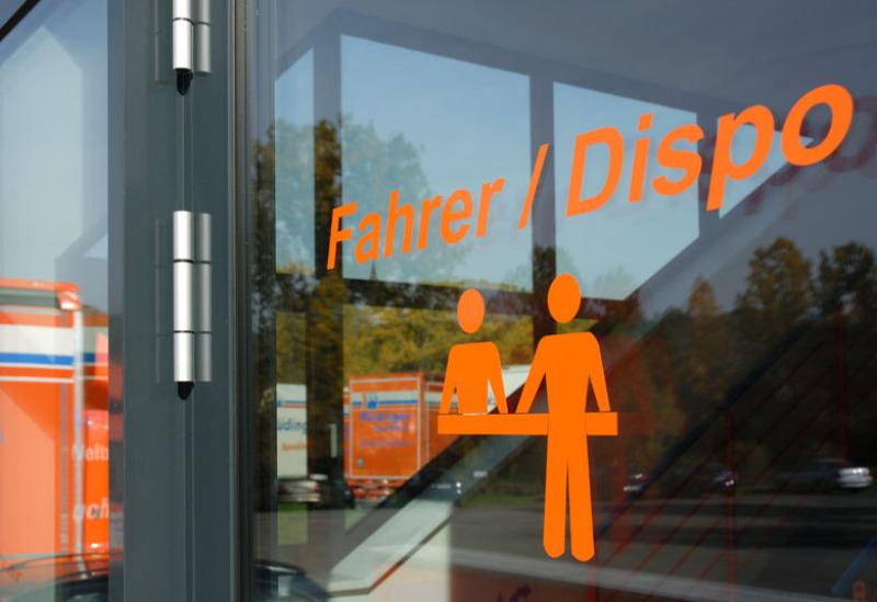 """Riesig groß sind die beiden Worte """"Fahrer"""" und """"Dispo"""" fotografiert. Dazu symbolisiert ein Piktogramm zwei Personen an einer Theke. Die Farbe des Hinweises auf dem Glas der Eingangstüre ist orange."""