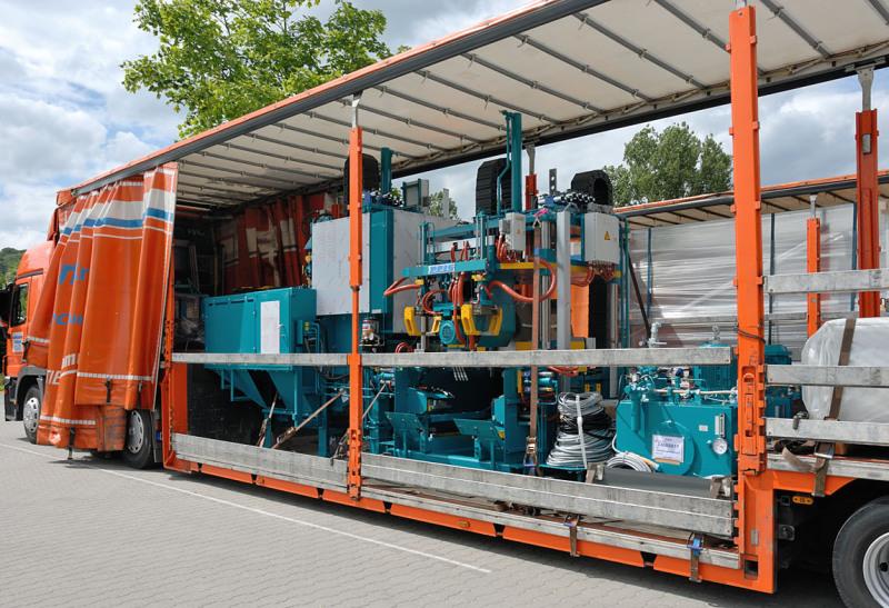 Bildfüllend sieht man einen 40-Tonnen-Lkw der Spedition mit einem ausgefahrenen Kran- Arm. Die Plane des Planentiefladers ist geschlossen und auf ihm sieht man ein Bild, das aussieht wie die geladene Ware innen. Am Kran hängt Ware.