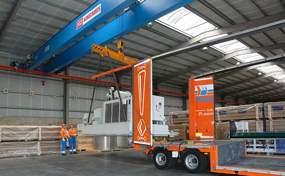 Ein 34-Tonnen-Kran in einer Lagerhalle hat eine sehr große Maschine aufgehängt. 2 Mitarbeiter in der Spedition, in orange-blauer Kleidung und mit Helm navigieren sie auf einen Lkw, dessen hinteres Ende rechts zu einem Drittel sichtbar ist.