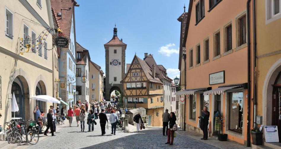 Ein touristisches Bild von Rothenburg ob der Tauber bei Sonnenschein, blauem Himmel und weißen Wolken. Der Blick geht zu einem mittelalterlichen Turm und mehreren historischen Gebäuden hin. Viele Touristen kann man erkennen.