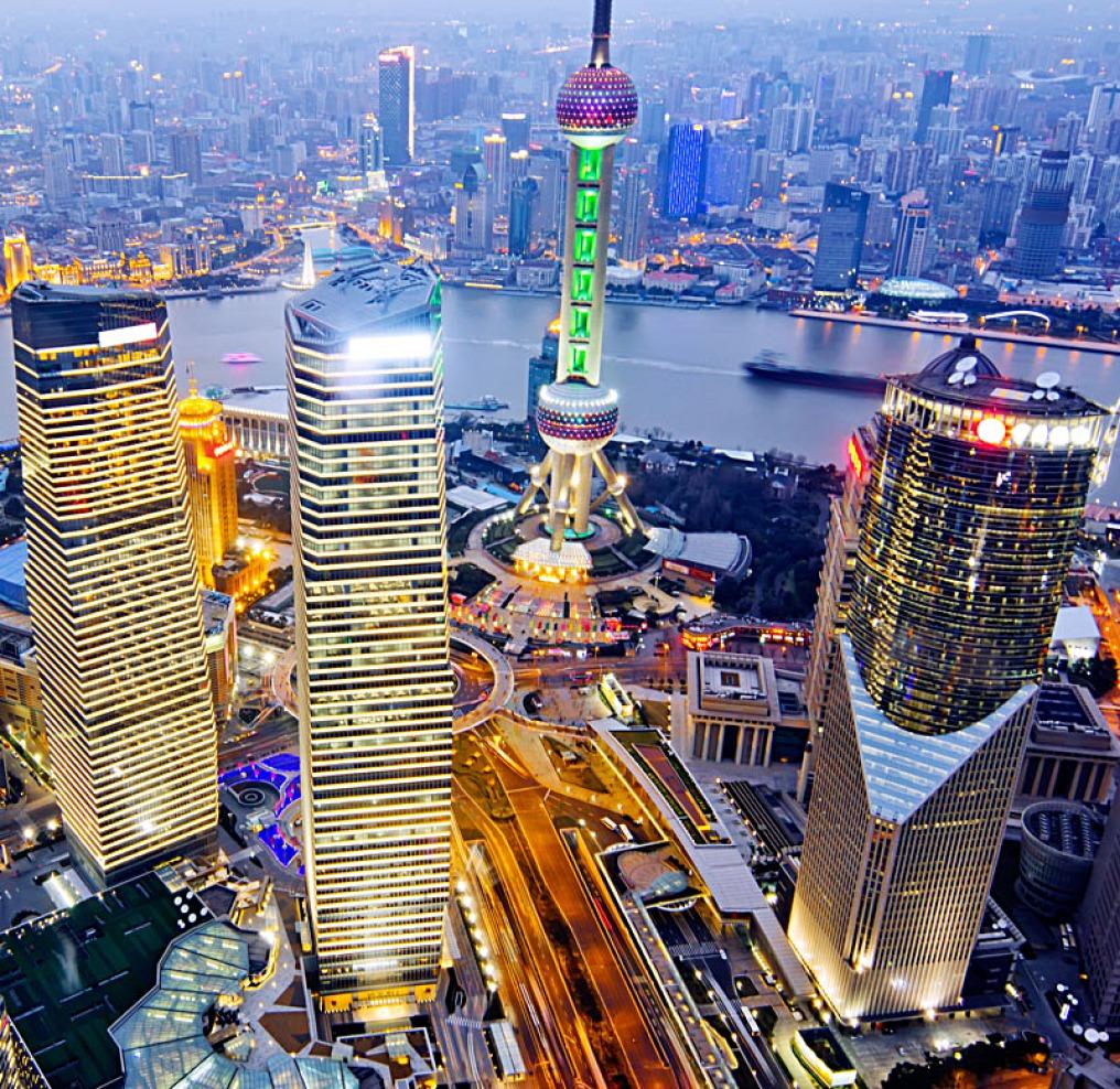 Eine Luftaufnahme ist in der Nacht über die Hochhäuser von Shanghai hinweg Richtung Fluss und dem gegenüberliegenden Stadtteil geschossen. Die Fenster der Wolkenkratzer sind hell erleuchtet.