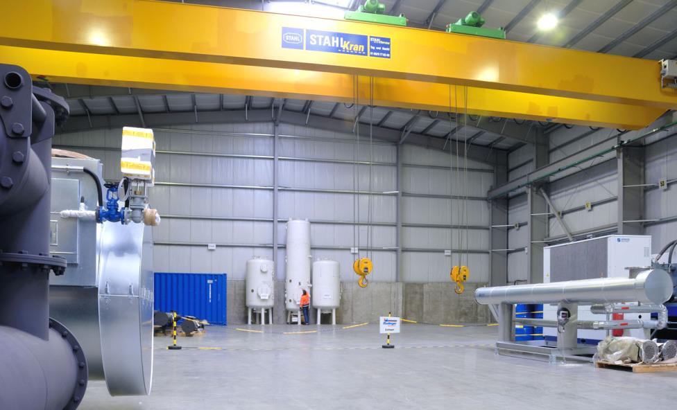 Man sieht das Zolllager der Spedition hinter einer Absperrung durch eine Kette. Darüber ist ein gewaltiger 32-Tonnen-Kran sichtbar. Im Zolllager befinden sich einige Maschinen und Maschinenteile.