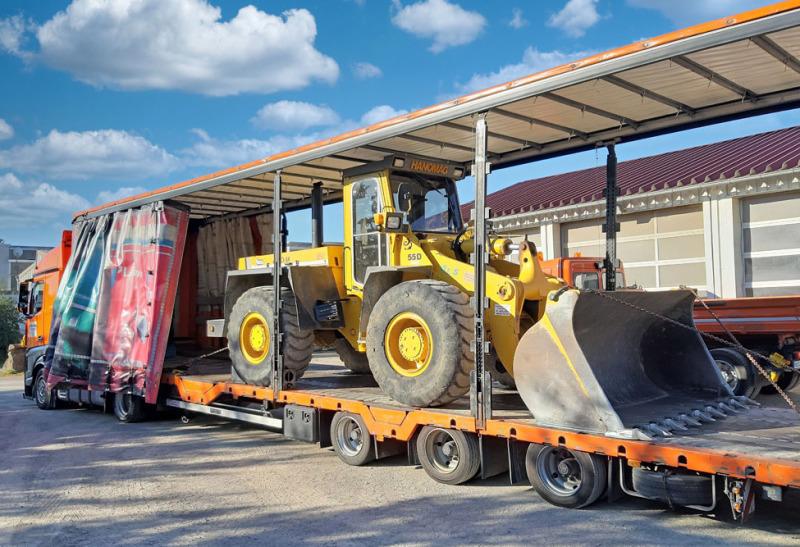 Im Bild ist ein kleiner Lkw mit weißer Fahrerkabine und hinten einer offenen Ladebordwand. Die Plane ist orange, auf der waagrechten Ladebordwand steht eine Palette mit Ware.