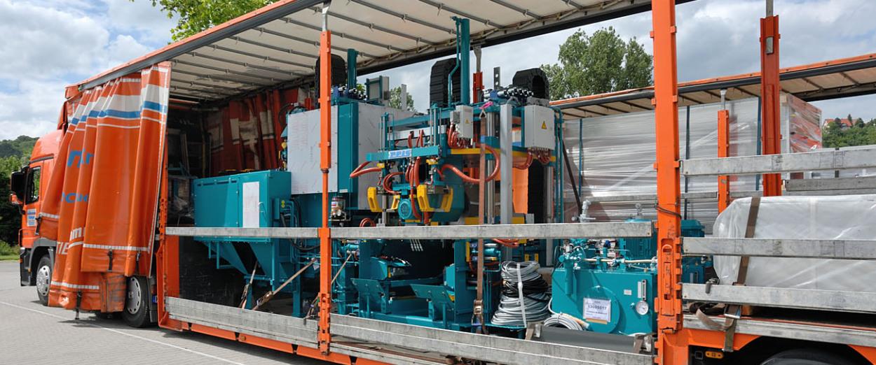 Auf einem Spezial-Plantieflader für Transporte für den Anlagenbau sieht man auf der Ladefläche – bei zurückgezogener Plane – eine komplexe Anlage. Der Lkw ist  von schräg hinten fotografiert.