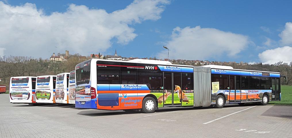 5 Busse, die im Halbkreis aufgestellt sind, 4 von der Rückseite, einen von schräg rückwärts in seiner ganzen Länge. Es ist ein besonders langer Gelenkbus voller sympathischer Werbung. Dahinter Burg und Kirche Krautheim.
