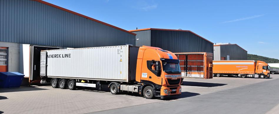 Ein Lkw für Container-Transport steht rückwärts an einer Rampe der drei Lagerhallen im Bild. Es ist die Halle vorne. Im Hintergrund sieht man einen zweiten Lkw, ein Planentieflader, in der Mitte ist offener Anhänger.