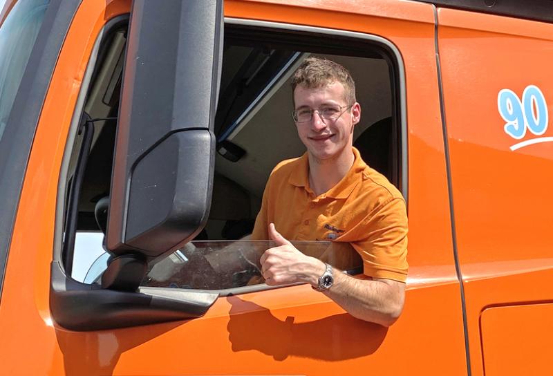 2 Azubis in orange/blauem Outfit stehen bequem vor einer Zugmaschine und schauen zum Fotografen und lächeln.