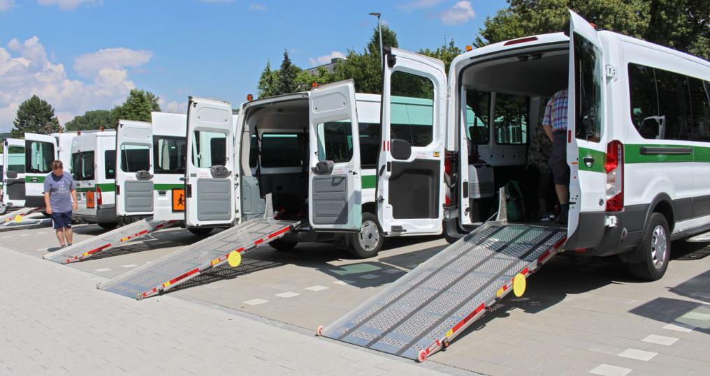 Man sieht 5 Behinderten-Busse, davon sind bei 4 die Rampen ausgefahren. Man sieht die Fahrzeuge von der Rückseite. Zwei Menschen arbeiten dort.
