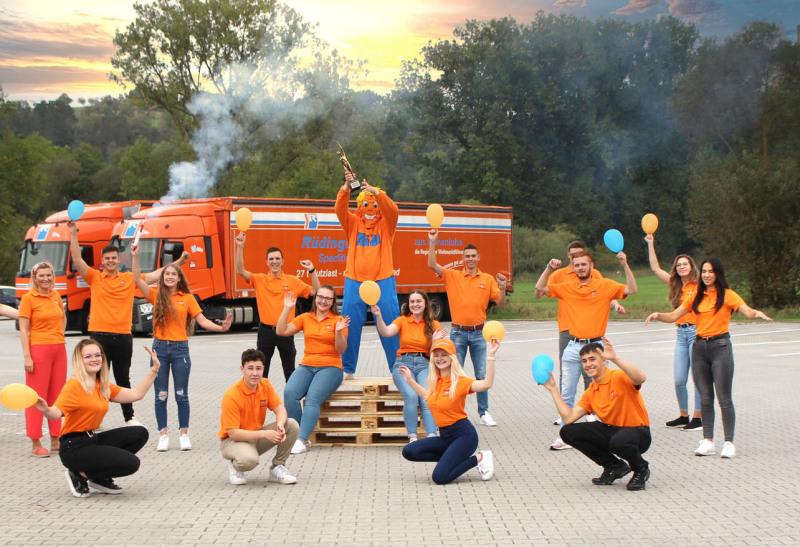 Runde 25 Azubis stehen, zum Teil in typischer blau/orangener Kleidung, zum Teil aber auch individuell gekleidet vor der Zugmaschine eines Planentiefladers. Die ein Hälfte steht, die andere kniet. Alle lachen oder schauen fröhlich.