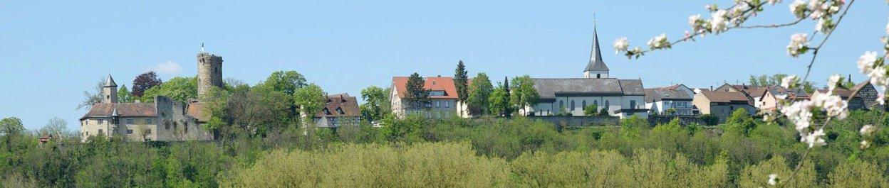 Krautheim, Sitz der Spedition in Baden-Württemberg: Links ist die Burg, in der Mitte die Kirche, rechts Häuser, vorne ist hellgrüner Wald, der Himmel ist blau und wolkenlos, ein Blütenzweig ist am rechten Bildrand des extremen Querformats.