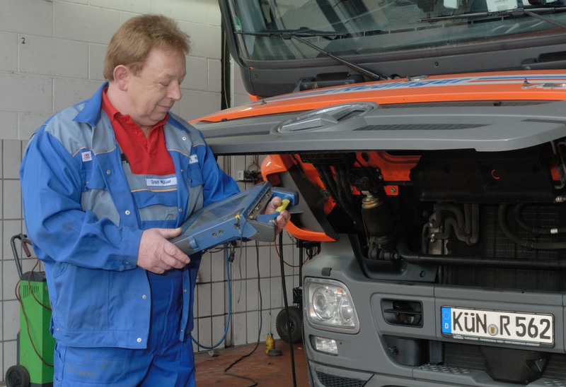Ein Kraftfahrzeugmeister in blauer Latzhose und blauem Arbeits-Jackett steht vor der geöffneten Motohaube eines Lkw vorne und sieht in ein Messgerät, das er in der Hand hält.