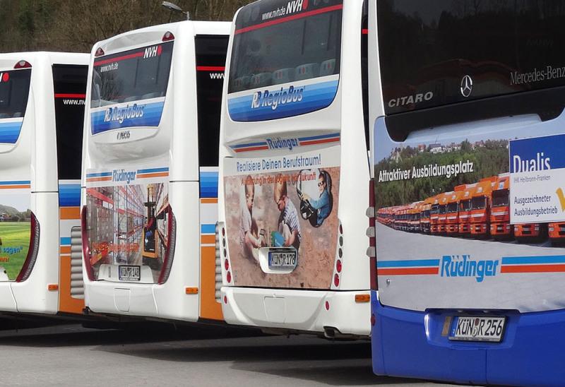 Man blickt auf die Rückwand von 4 Stadtbussen. Auf allen Bussen besteht die Werbung für die Rüdinger- Spedition aus bunten Fotos mit Text, zusammengestellt als Collagen.