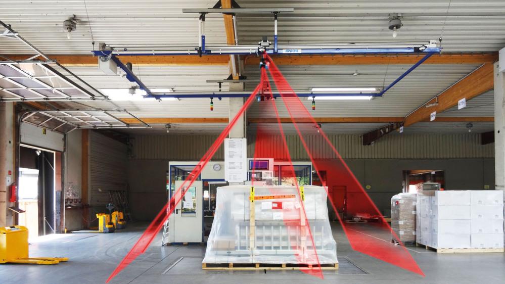 Man sieht eine Kehrmaschine, XXL-Stückgut auf einer Bodenplatte in einer Speditionshalle. Ein stilisierter Laserstrahl geht in drei Sektionen vom oberen Rand des Bildes zu den Eckpunkten der Platte.