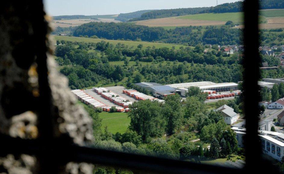 Man sieht vom Turm der nahen Burg Krautheim auf das Betriebsgelände der Spedition Rüdinger. Im Vordergrund sind historische Burgfenster-Gitterstäbe im Bild und Mauerwerk links und rechts. Im Hintergrund ist viel hügelige und bewaldete Landschaft.