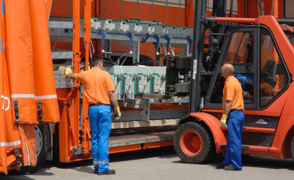Man sieht bildfüllend, wie 2 Mitarbeiter prüfen, wie man eine große Maschine, die auf dem Stapler bereits halb im LKW ist, am besten verstaut. Die Sonne scheint, alles ist in orange und blau.