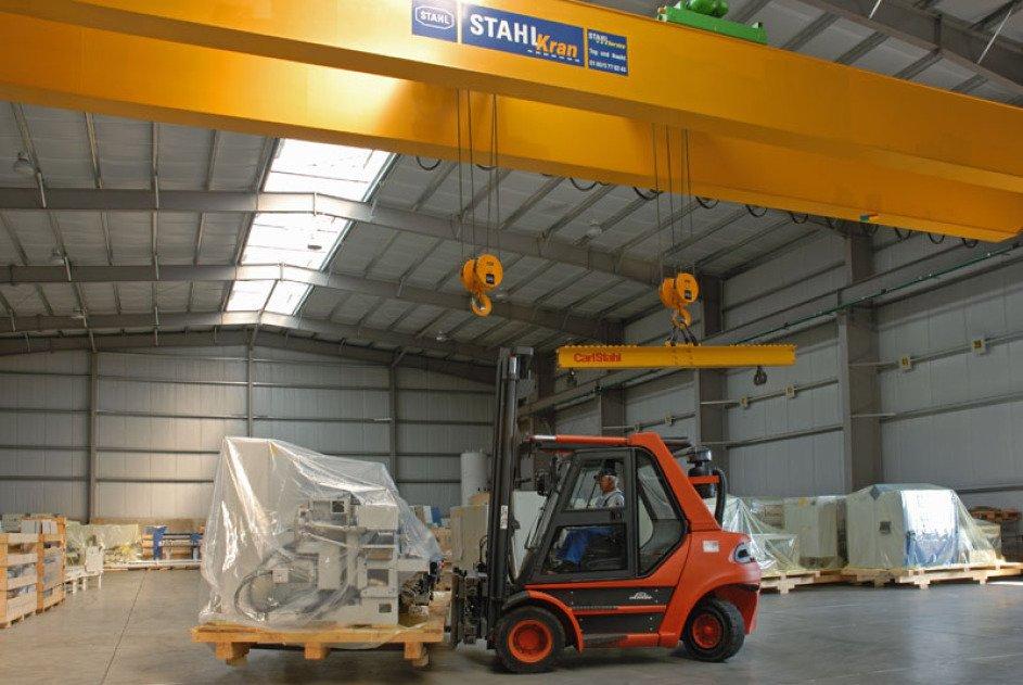 Unter einem gelben Hochleistungskran in einer Lagerhalle sieht man einen orangenen Stapler, der eine in eine Folie verpackte Maschine geladen hat. In der Bildmitte sieht man 2 riesige Haken vom Kran herunter hängen.