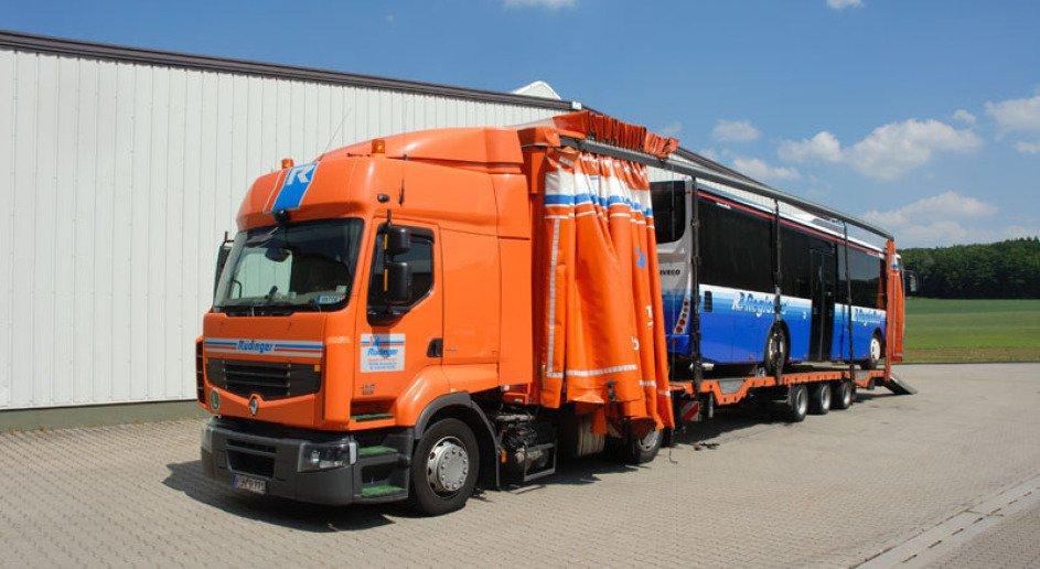 Man sieht einen langen, orangenen LKW der Spedition. Links ist eine Lagerhallenwand, rechts im Hintergrund Wiese und Wald, oben blauer Himmel mit Wolken. Der LKW hat einen blauweißen Stadtbus geladen, der komplett aufgefahren ist.