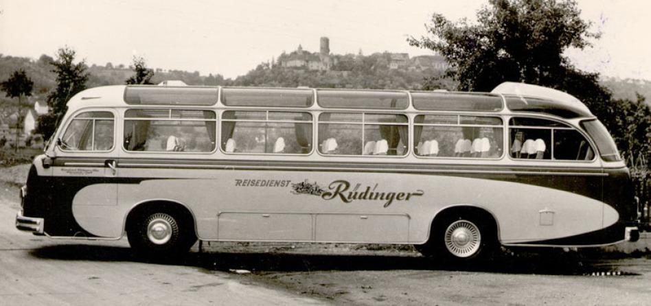 """Ein historisches Foto zeigt einen historischen Reisebus mit der Aufschrift """"REISEDIENT Rüdinger"""" vor der Burg Krautheim auf einem Hügel. Niemand sitzt im Bus, die Glasfläche reichen von der Seite bis nach oben."""