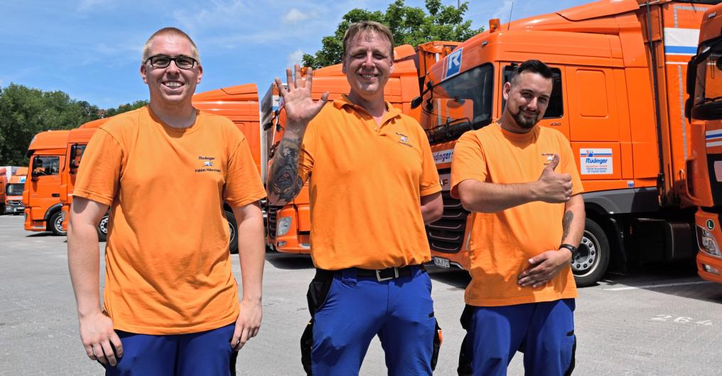 """Ein LKW-Fahrer sitzt in seinem Führerhaus des orangenen LKW der Spedition und schaut zur Kamera, während er den Daumen, Symbol für """"alles okay"""" zeigt. Der LKW-Fahrer legt den Ellenborgen auf."""