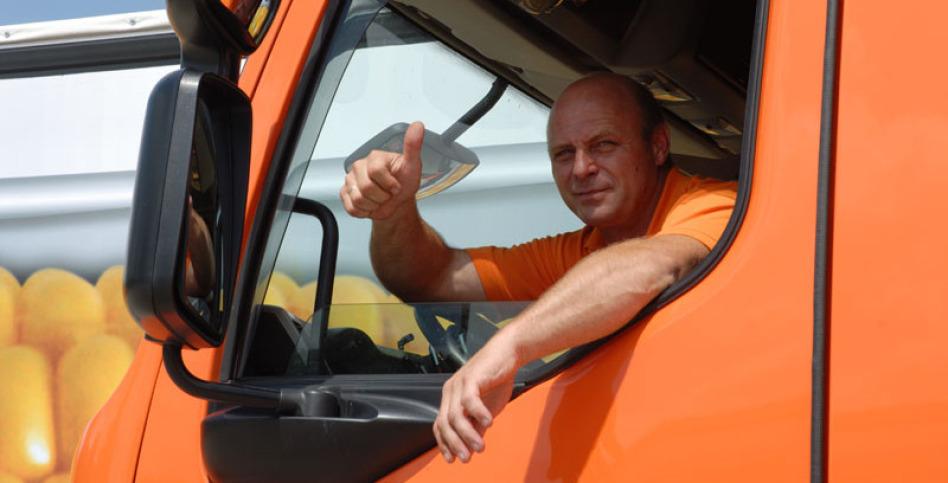 """Ein Lkw-Fahrer schaut durch sein Seitenfenster zum Fotografen und mimt den Daumen nach oben: """"Alles okay!"""". Den linken Arm lehnt er auf der Scheibe auf und streckt ihn auch heraus,"""
