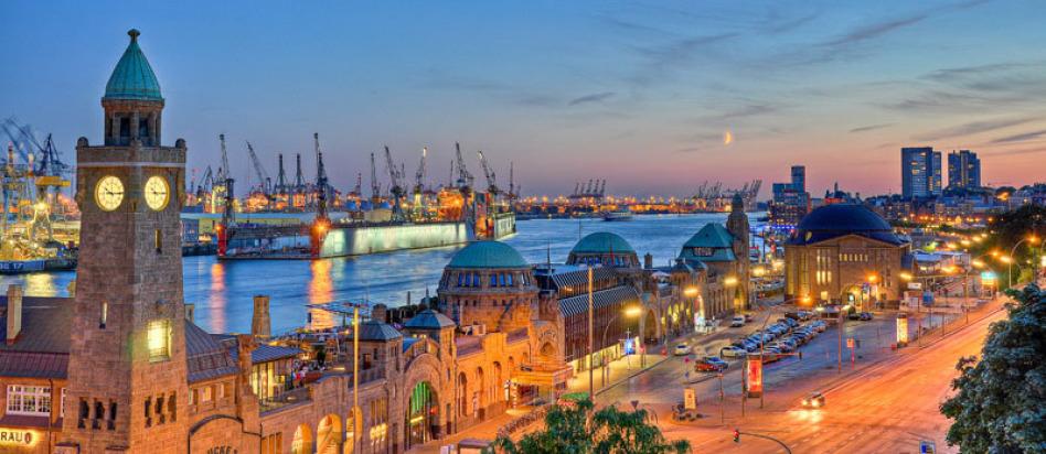 Man sieht den Hamburger Hafen am Abend. Alle Lichter sind erleuchtet. Man erkennt Wasser sowie ein Schiff. Am Himmel kann den Mond erkennen. Es sind Blau- und Gelbtöne.