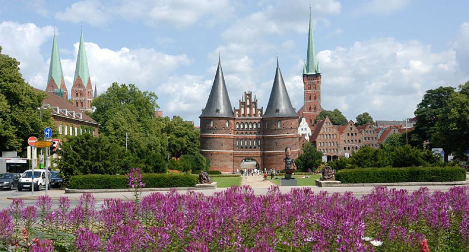 Der Blick geht auf das Holstentor in Lübeck. Im Vordergrund blühen lila Blumen, man erkennt drei Kirchtürme, der Himmel ist blau und da sind Wolken, die Sonne scheint. Die Bäume stehen voll im Sommerlaub.