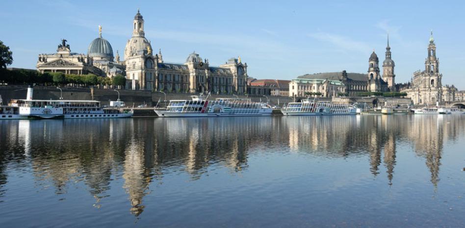 Es ist die Schokoladenseite von Dresden über die Elbe hinweg fotografiert. Wasser macht 50 Prozent des Fotos aus und man sieht viele historischen Gebäude zwischen dem Zwinger und der Liebfrauenkirche.