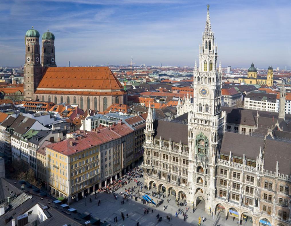 Eine Luftaufnahme von München in der auf der linken Seite die Frauenkirche, auf der rechten das historische Rathaus dominieren. Die Sonne scheint, der Himmel ist tels blau, teils verschleiert.