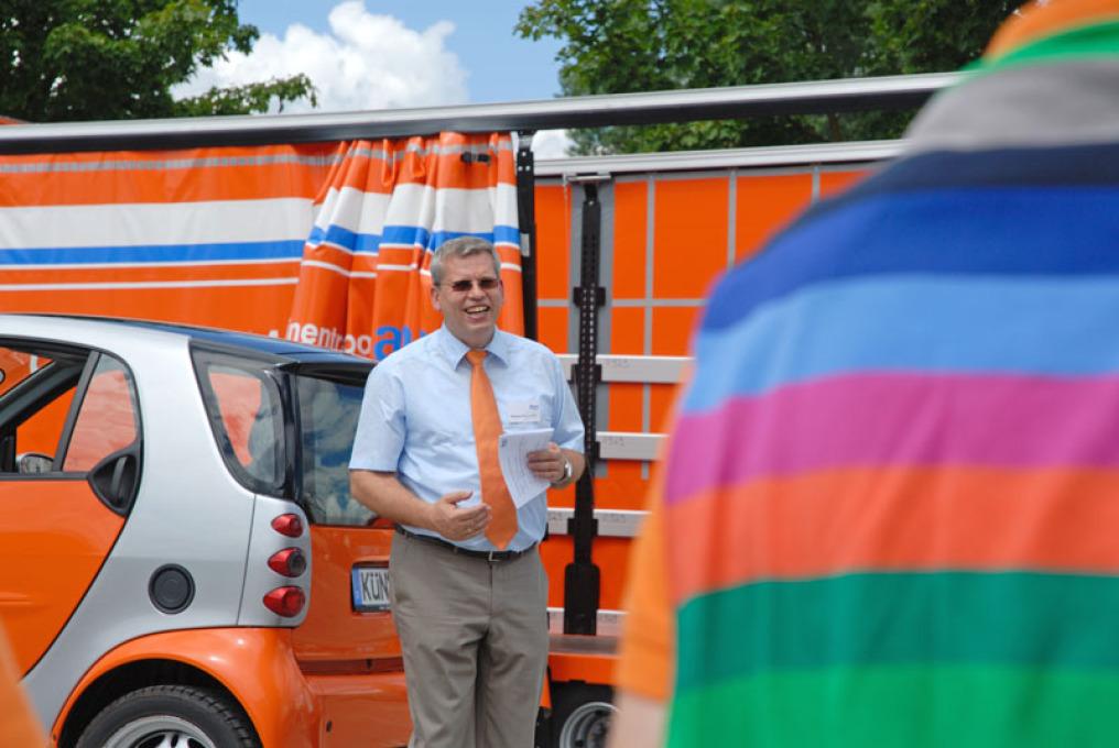 Der Firmenchef der Spedition bis zu den Knien. Er hält ein Papier in der Hand un referiert zur Kamera. Links hinter ihm ist ein orangener Smart, dahinter ein Lastzug mit offener Plane. Im rechten Bilddrittel verdeckt die Rückansicht eines bunten T-Shirts.