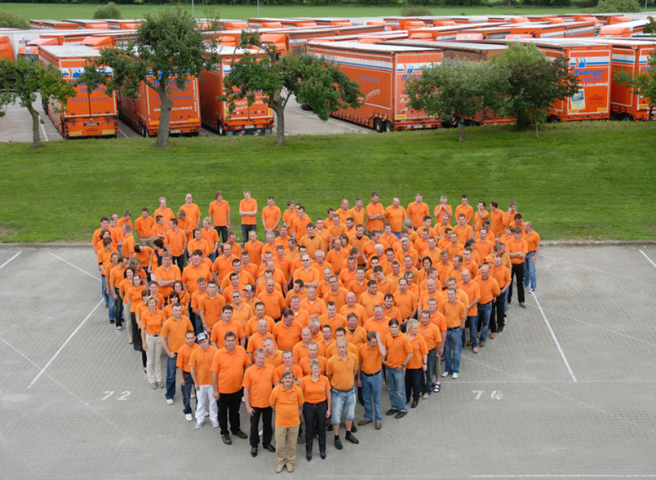 Es ist ein Foto aus einem der Gebäude der Spedition. Rund 100 Mitarbeiter in orangener Kleidung bilden ein Herz auf dem Hof des Unternehmens. Dahinter ist eine 20 Meter breite Grasfläche, dahinter stehen rund 50 große Lkw. Alle Mitarbeiter blicken zum Fot