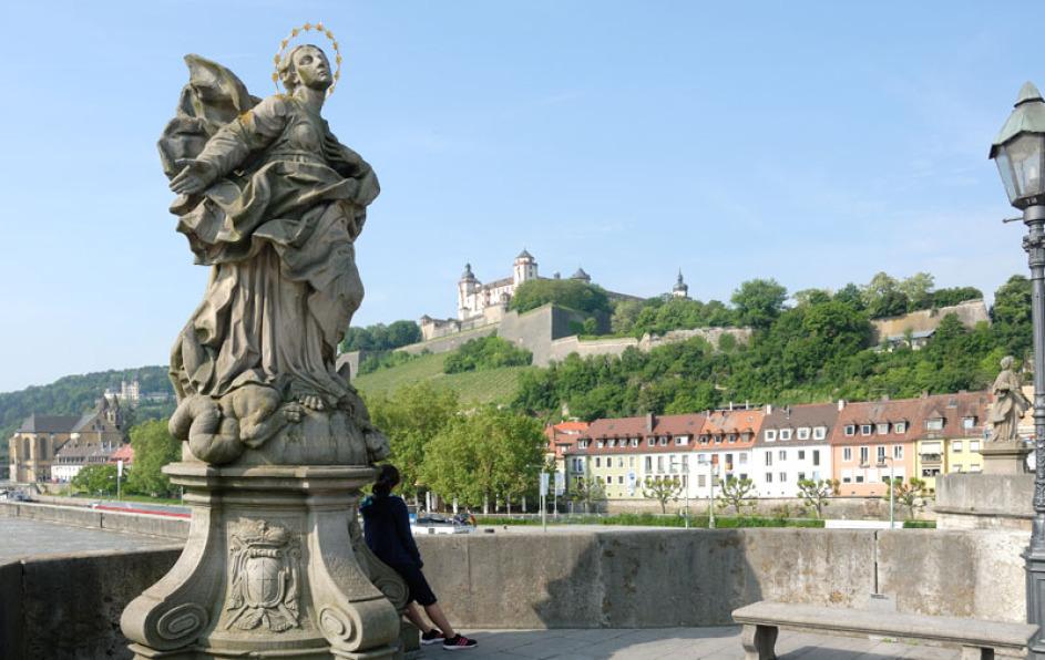 Man sieht von einer der Mainbrücken hinauf zur Marienfeste in Würzburg. Rechts vorne ist eine halbe Lampe im Foto, links eine riesige historische Heiligenfigur. Zwischen Brücke und Schloss sind Häuser, man sieht den Main.