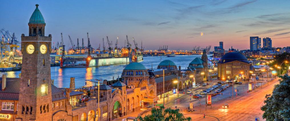 Der Hamburger Hafen in der späten Dämmerung: Man sieht die Wahrzeichen der Stadt, im Hintergrund sieht man Kräne. Die Gebäude sind hell erleuchtet. Im Hintergrund ist der Mond schwach zu sehen.