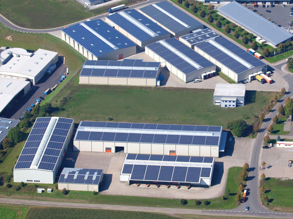 Aus der Luft fasst senkrecht darüber fotografiert sieht man 12 Lagerhallen, die komplett mit Photovoltaikanlagen bestückt sind. 2 Straßen sind unten und rechts, zwischen zwei Bereichen ist eine Grünfläche.