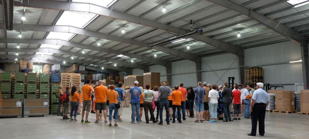In einer großen Lagerhalle steht eine große Besuchergruppe im Halbkreis. Man sieht links hinten viele Waren, ebenso am rechten Rand der Halle. Hinter allen Menschen steht der Seniorchef von Rüdinger, man sieht ihn von der Rückseite.