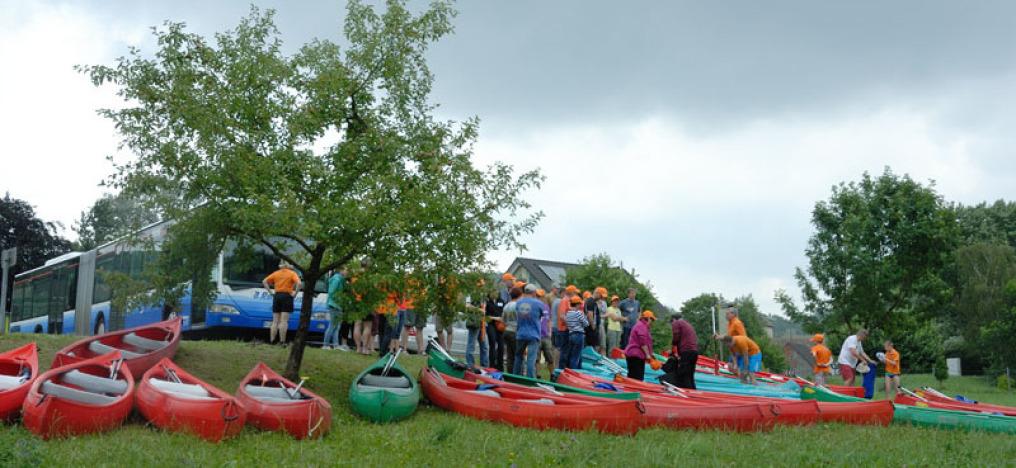 An einem bedeckten Tag sind im Vordergrund etwa 20 Kanus auf einer Wiese mit Bäumen. Man sieht etwa 25 Menschen, alle mit einem orangenem Käppi auf, Links oben im Hintergrund steht ein langer Regionalbus.