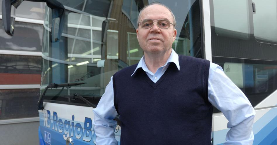Ein Busfahrer mit blauem Hemd und dunkelblauem Polunder steht vor einem Regio-Bus, von dem man fast nur die Frontscheibe erkennt. Der Bus selbst steht vor einer Wartungshalle, von der man das Tor sieht.