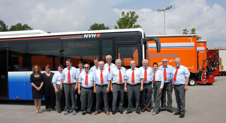 Vor der vorderen Hälfte eines blauen Busses links und mehreren Lkw-Anhängern im Hintergrund rechts steht eine Gruppe von etwa 15 Busfahrern in einheitlicher Kleidung. Links stehen 2 Frauen: ein Gruppenbild.