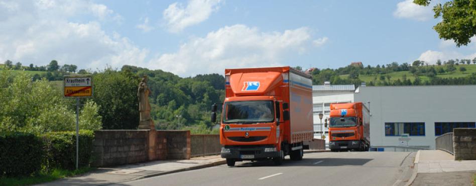 2 Rüdinger-Lkw fahren auf einer alten Brücke in Richtung Betrachter. Vorne ist es ein kleiner 12-Tonnen-Lkw, dahinter kommt ein 40-Tonnen-Lkw der XXL-Klasse. Links sind Ortsschild und eine historische Skulptur sichtbar.