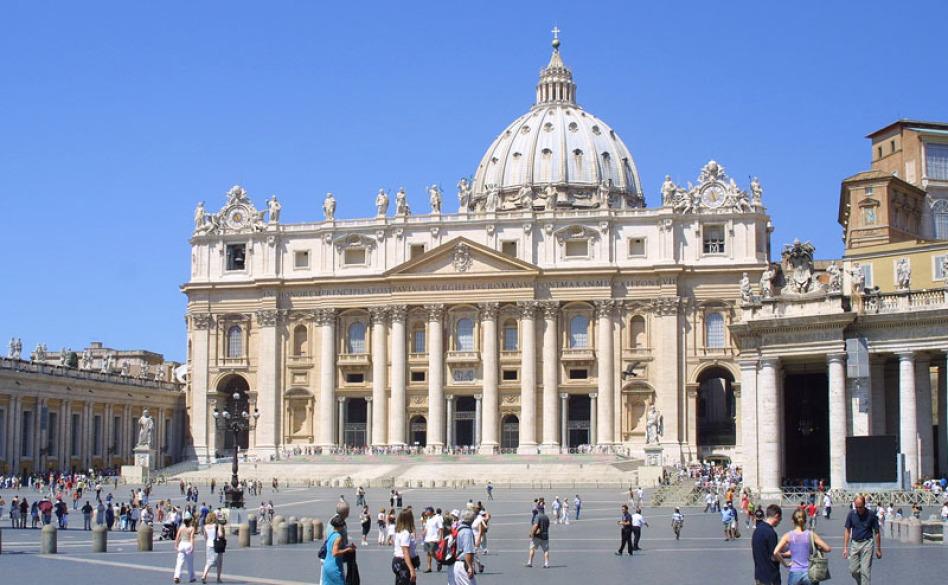 Im Bild ist der Petersdom in Rom mit seinem Vorplatz und relativ vielen Menschen davor. Der Himmel ist wolkenlos und blau, die Sonne scheint, die Perspektive ist vom Boden fotografiert.