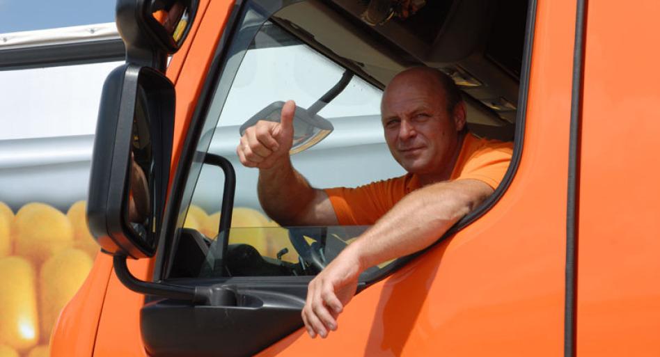 """Man sieht die Fahrerkabine eines LKW, allerdings sehr nah. Darin sitzt ein Mitarbeiter mit orangenem Shirt und schaut zur Kamer. Er hebt den Daumen zum Zeichen """"Alles okay!""""."""