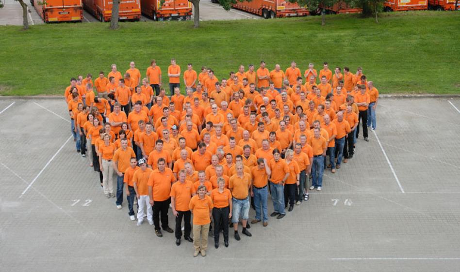 Runde 50 bis 70 Mitarbeiter auf dem Hof der Spedition bilden ein Herz und schauen lächelnd zur Kamera. Dahinter ein breiter Grünstreifen, Dahinter sind Lkw. Fotografiert ist das Bild aus dem 1. Stock.