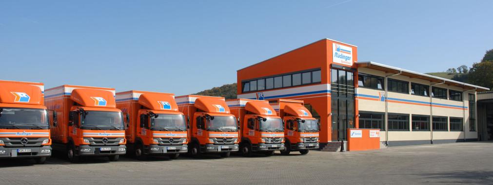Das extrem breite Querformat-Foto zeigt in der linken Hälfte 6 kleinere Lkw in der rechten Hälfte das komplette Verwaltungsgebäude der Spedition. Die Lkw sind orange, das Gebäude ist sehr modern und auch zum Teil orange.