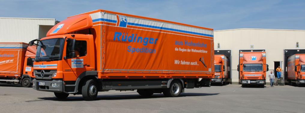 """Ein 12-Tonnen-LKW posiert vor weiteren 4 12-Tonnern im Hintergrund an den Rampen einer Umschlaghalle. Er steht diagonal zu allen anderen Fahrzeugen und trägt die Aufschrift """"aus Hohenlohe der Region der Weltmarktführer""""."""